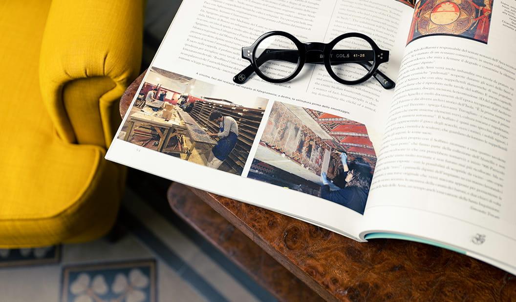 Lesca Burt black eyeglasses on magazine
