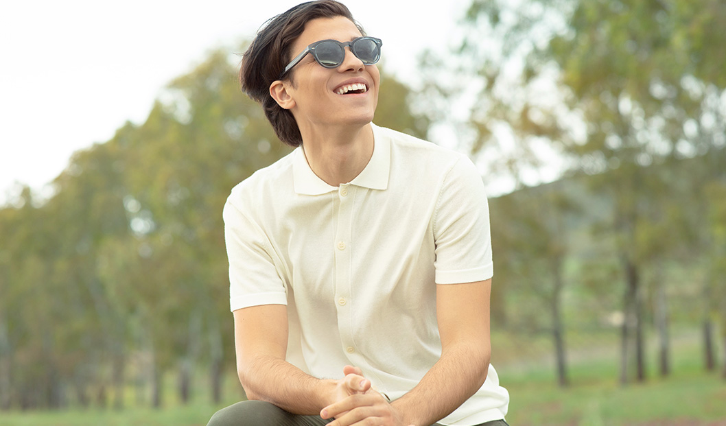 Young man outdoors wearing Oliver Peoples sunglasses | Mia Burton Magazine