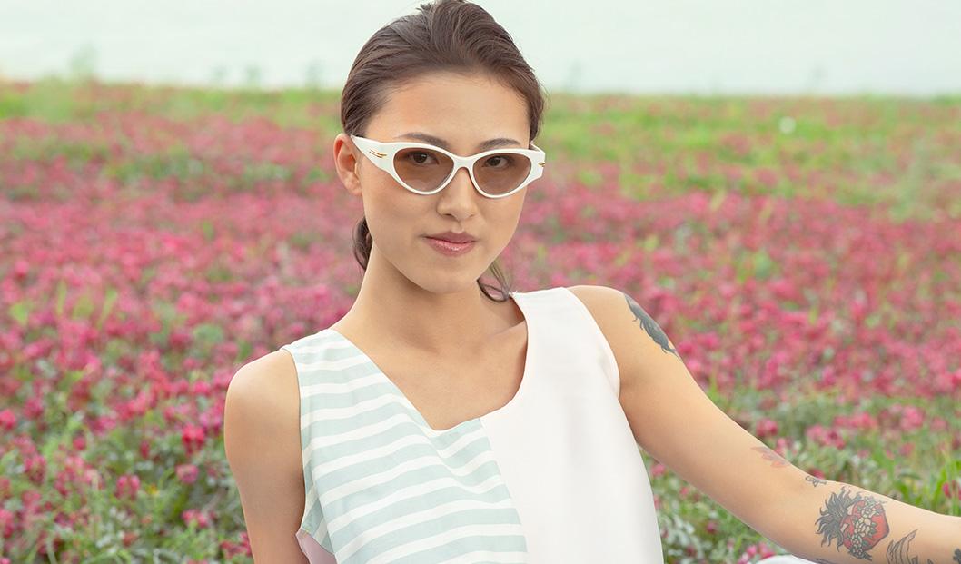 Young woman wearing Bottega Veneta sunglasses in a field in bloom |